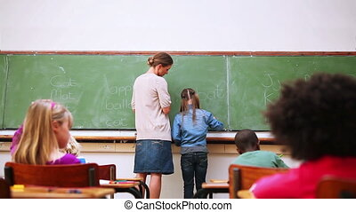 Pupil and teacher standing upright in the classroom