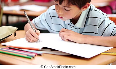 Smiling boy writing on his notebook in the classroom