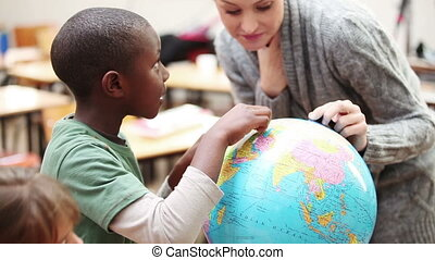 Pupil and teacher looking at a globe