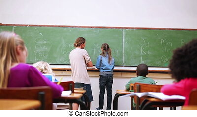 Rear view of a pupil writing on the blackboard in the...