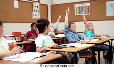 Smiling pupils raising their arms in the classroom