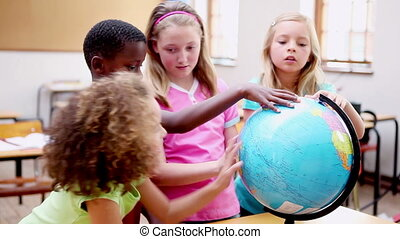 Smiling children looking at a globe in the classroom