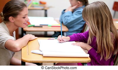 Happy teacher helping a pupil