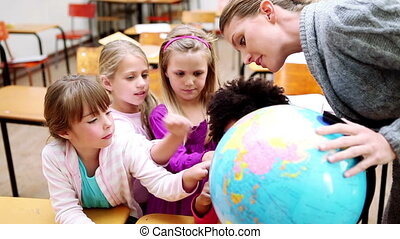 Pupils pointing at a globe in the classroom