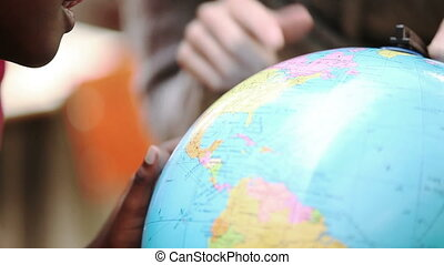 Teacher pointing the globe in the classroom