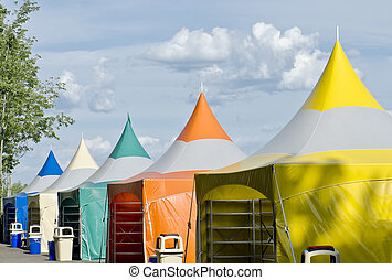 Colorful Tents - Five colorful carnival tents against a blue...