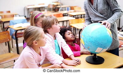 Cute children looking at a globe in the classroom