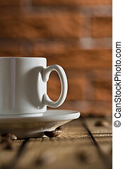 white coffee cup on a background of a brick wall