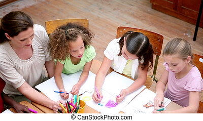 Smiling pupils coloring together in the classroom