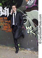 Young businessman talking on the phone in an urban area with...