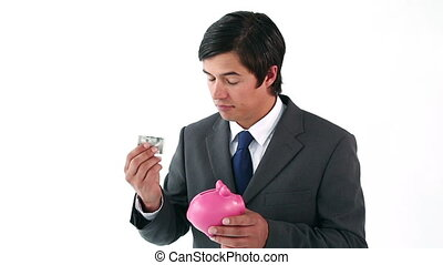 Businessman putting notes in a piggy bank against a white...
