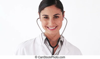 Smiling doctor showing her stethoscope against a white...