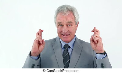 Mature man crossing his fingers against a white background