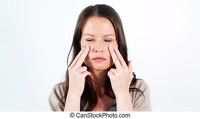 Woman massaging her face against a white background