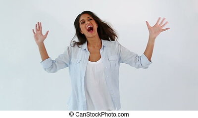 Happy woman raising her arms against a white background