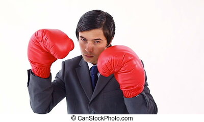 Serious businessman using boxing gloves against a white...