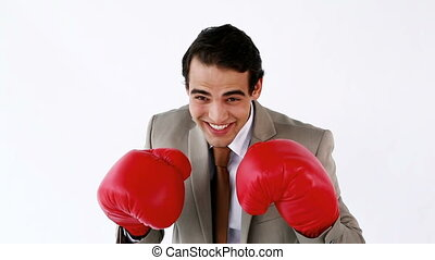 Smiling businessman using boxing gloves against a white...
