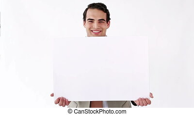 Businessman holding a blank poster against a white...