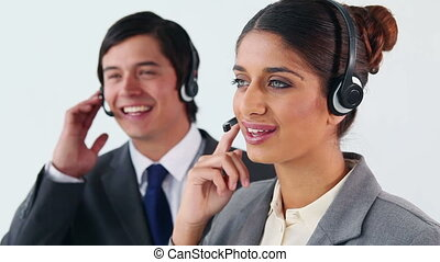 Smiling call centre agents working together against a white...