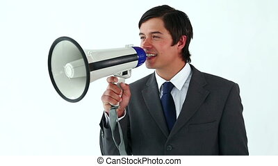 Smiling man talking with a megaphone against a white...