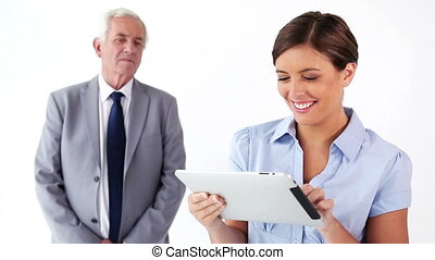 Smiling woman using a tablet pc with a colleague against a...