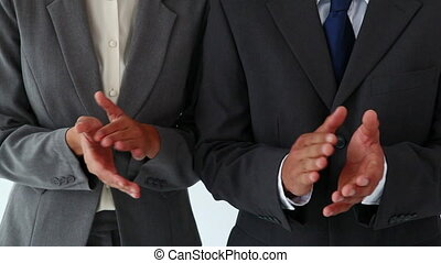 Business people clapping against a white background