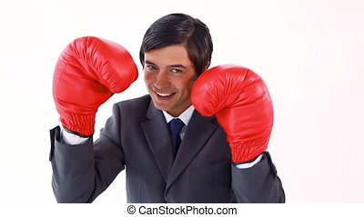 Happy executive using boxing gloves against a white...