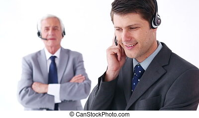 Business people working while using headsets against a white...