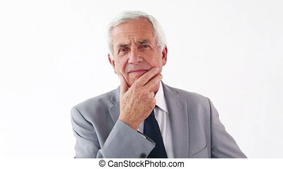 Mature man placing his fingers on his chin against a white...