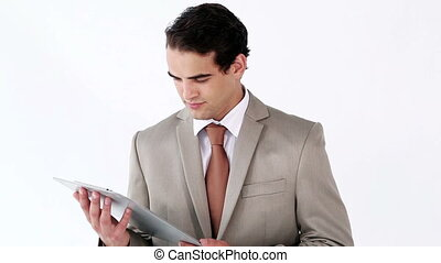 Serious businessman using a tablet pc against a white...