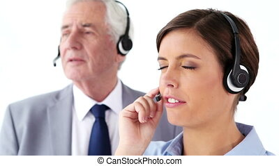 Business people using headsets together against a white...