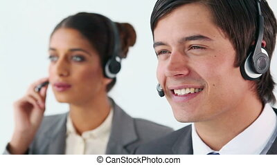 Smiling call centre agents using headsets against a white...