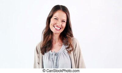 Happy woman standing upright against a white background