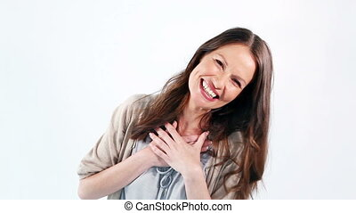 Smiling woman placing her hands on her chest against a white...