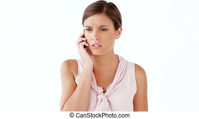 Happy woman using a mobile phone against a white background
