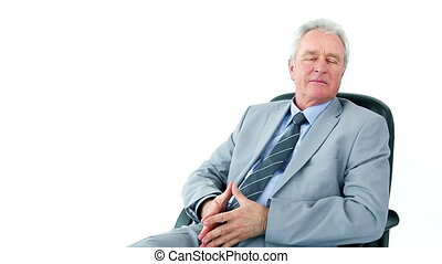 Serious businessman sitting on a swivel chair against a...