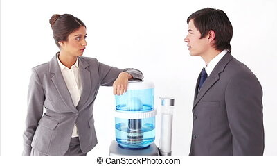 Colleagues chatting next to the water cooler against a white...