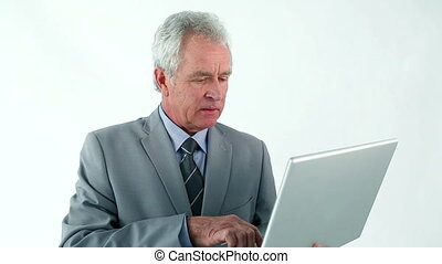 Serious businessman holding a laptop against a white...