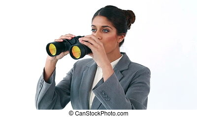Happy businesswoman looking through binoculars against a...