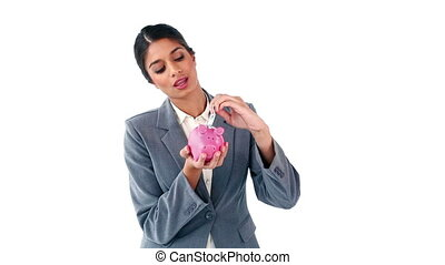 Smiling secretary holding a piggy bank against a white...