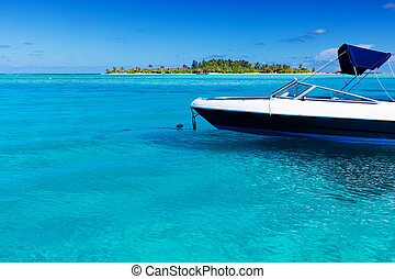 Boat in tropical lagoon with island in background - Boat in...