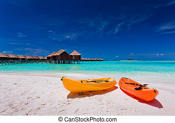 Colourful kayaks on the tropical beach - Two colourful...
