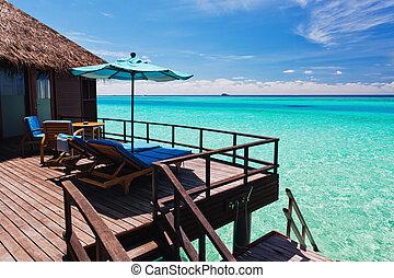 Overwater villa balcony overlooking green lagoon - Overwater...