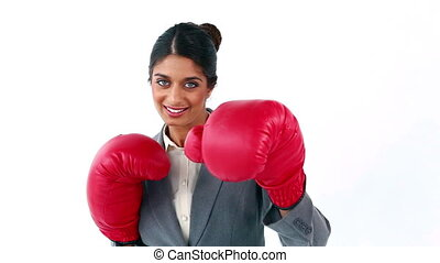 Smiling secretary using boxing gloves against a white...