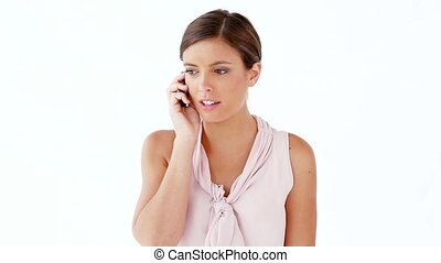Surprised brunette woman calling against a white background