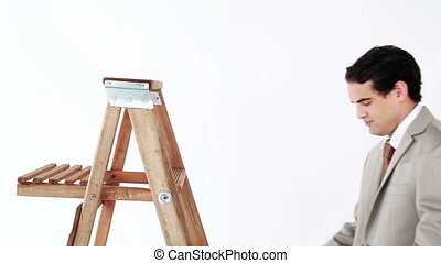 Smiling man getting up on a ladder against a white...