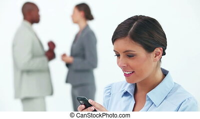 Businesswoman smiling while reading a text message with her...
