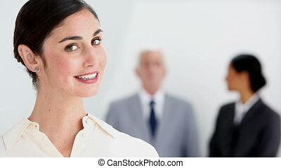 Smiling businesswoman posing with colleagues talking against...