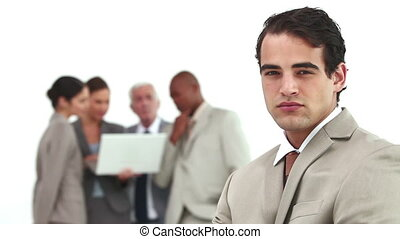 Serious businessman with his co-workers in background using...