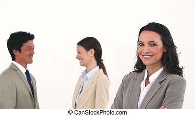 Businesswoman posing with her colleagues talking in...